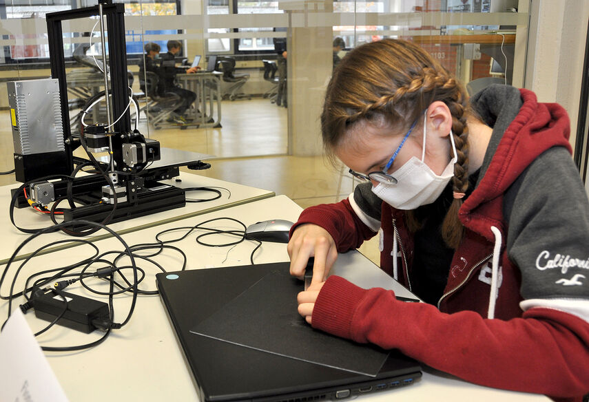 Eine Schüler arbeitet an einem 3D Drucker an einem Prototyp.