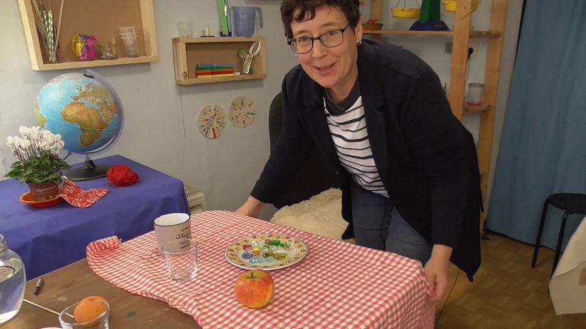 Melanie Hecker versucht einen Zaubertrick an einem gedeckten Tisch.